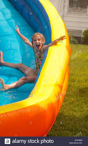 family water slide in back yard at home with water in summer