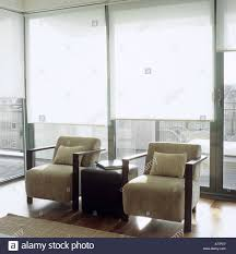 pair of contemporary armchairs in a light living room with white