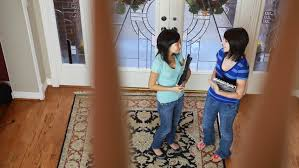 Banister Clips Two Teenage Girls Standing In The Foyer Of An Affluent Home