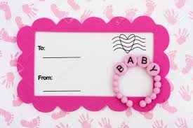 a white postcard with a pink border and baby bracelet on a hand