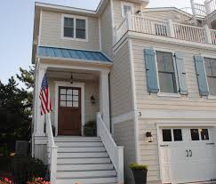 beach house exterior blue metal room tan siding carriage door