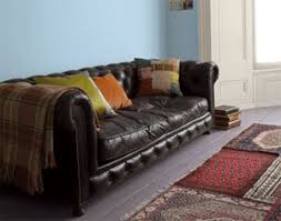 brown sofa and ethnic carpets to match blue sky wall painting