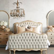 nice brushed bronze antique chandelier over queen tufted bed with