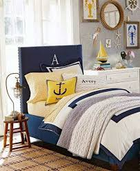 nautical themed bedroom with wall accessories and navy blue bed