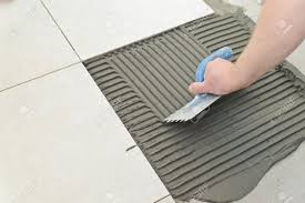 Laying Ceramic Floor Tile Laying Ceramic Tiles Troweling Mortar Onto A Concrete Floor