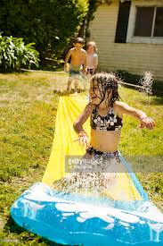 kids play in backyard water slide stock photo getty images