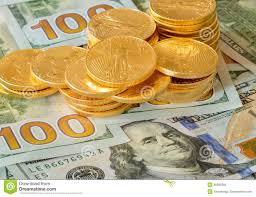 gold coins stacked on design 100 dollar bills stock photo