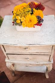 chic furniture with a golden yellow and rustic red flower arrangement