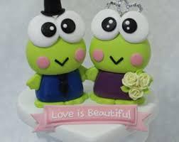 a frog couple wedding cake topper orange roses