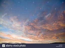 small clouds of pastel colours spread across the evening sky over