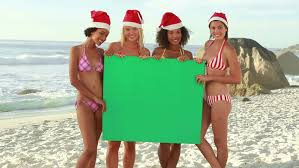 Four girls wearing christmas hats at the beach…  Royalty Free Video