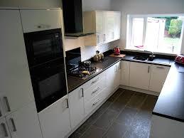 cream painted kitchen cabinets kitchen catle laminate wooden floor black appliances cream