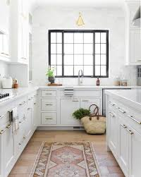 white kitchen cabinets with window trim like black window trim white subway backsplash door pulls