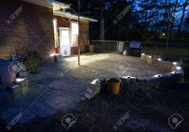 large patio with sand set bricks and solar lights in the night