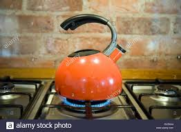 retro orange kettle on stainless steel gas stove against a rustic