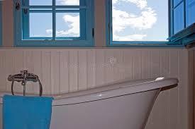 retro wood paneling retro bath white wood paneling and blue windows stock photo
