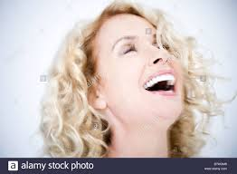 middle aged a confident and attractive middle aged woman in white laughing