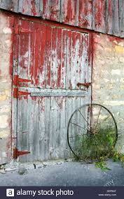Red Barn Door by A Rustic Old Barn Door With Peeling Red Paint Stone Walls And A