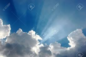 colorful blue sky with tiny clouds and sun rays stock photo