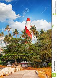 thangassery lighthouse on the cliff surrounded by palm trees and