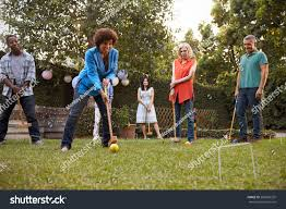 group mature friends playing croquet backyard stock photo