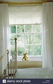 teddy bear on window sill of window with cream lace blind and