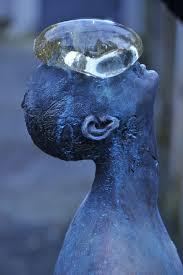 a giant glass raindrop balances on a bronze man u0027s face in ukraine
