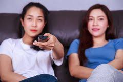 best sofa for watching tv two best friends watching tv with remote on sofa at home stock photo