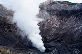 an awe inspiring plume of smoke and gas escape through a crater