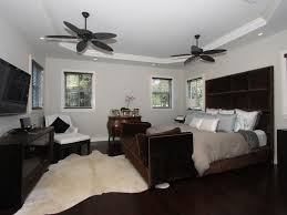 modern guest bedroom with ceiling fan wall mounted tv in coral