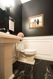 powder room with a high ceiling black walls and white wainscoting