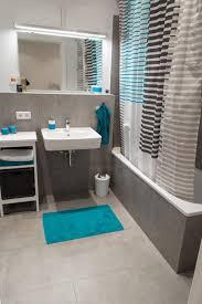einrichtung badezimmer graue fliesen graue badewanne blaue akzente durch teppich und