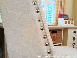 white upholstered desk chair with nailhead accent
