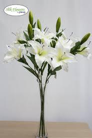 cream lilies in glass vase arrangement
