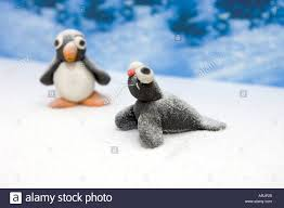 plasticine childs models of a penguin and a seal in a winter scene