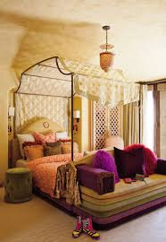 bedroom enchanting canopy bed for the mystical yet luxury canopy bed with campaign iron canopy and sheer yellow polka dot curtain orange patterned blanket round