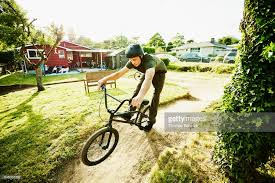 man riding bmx bike on backyard dirt track on summer afternoon