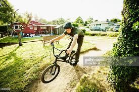 man riding bmx bike on backyard dirt track on summer afternoon