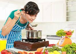 femme dans la cuisine femme goûte sa cuisine dans la cuisine banque d images et