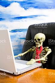 Skeleton Computer Meme - skeleton wearing tie in executive chair with laptop on desk stock