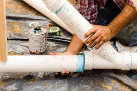 plumbing building contractor installing plastic drain pipe in
