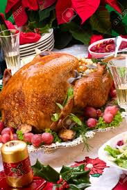 garnished roasted turkey on christmas decorated table with candles