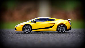yellow lamborghini yellow lamborghini gallardo scale model on black concrete road