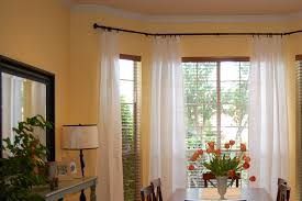 decorating bay window curtain rod with decorative cushions
