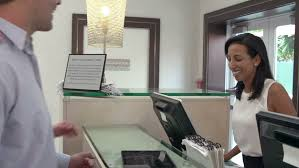 Hospital Reception Desk Patient And Nurse With Tablet Conversing At Hospital Reception