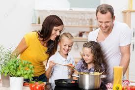 cuisine en famille heureux famille avec maman papa et deux jeunes enfants de
