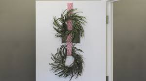 decor wreath hanger with green leaf decorationd and white front