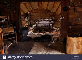stone fireplace with cast iron cooking utensils inside log cabin