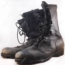 used motorcycle boots used black leather combat boots in front of white background stock