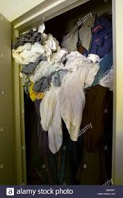 messy closet clothing spills out of full messy closet stock photo royalty free